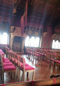 Ein Blick in den großen Festsaal mit der Burschenschaftsfahne. Die Raumausstattung bildet die idealisierte Vorstellung vom religiösen Mittelalter und den Kreuzzügen ab.