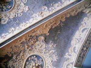 Im Zentrum findet man Medaillons mit Fruchtgehängen umrahmt von Knorpelwerk aus Voluten, Vögeln und Masken.