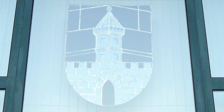 Das Wappen der Stadt zeigt eine Zinnmauer mit offenem Tor und dahinter einen spitzbedachten übereck stehenden Turm.