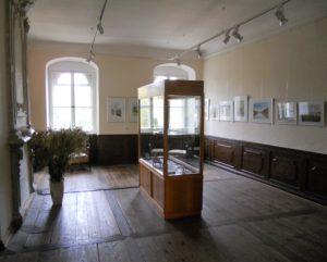 Die Räume des oberen Geschosses dienen als kleine Galerie und zeigen Arbeiten von lokalen Künstlern.