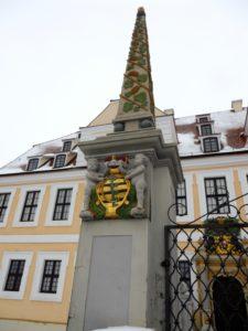 Zwei Obelisken flankieren das Haupttor zum Schloss. Unterhalb sind zwei Putten angebracht, die das sächsische Wappen tragen und den Herzogshut darüber halten.