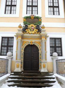 Den Eingang zum Schloss bildet das Stifterportal. Bekrönt wird es von zwei schwarzen Löwen, die die Wappen von Sachsen und Cleve, sowie des Stifts Merseburg flankieren. In der Inschriftentafel darüber wird Christian I. von Sachsen-Merseburg (1615-1691) als Bauherr genannt.