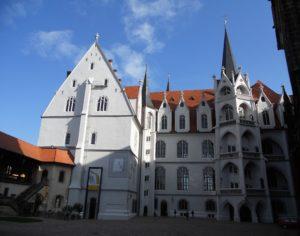 Auf dem Schlosshof: Ganz links ist ein Verbindungsbau zu sehen. Bis zu seinem Abriss 1863 befand sich dort ein Brennhaus, welches seit dem 18. Jahrhundert das Küchenhaus ersetzte. Hervorstechend aus der Hoffassade ist der Große Wendelstein, der das Haupttreppenhaus des Schlosses bildet und seinerzeit eine architektonische Meisterleistung war. Ganz rechts im Bild ist schon der Dom zu sehen.