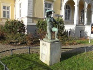 """Die """"Große Kniende""""(1935/36) von Georg Kolbe. Er schenkte die Skulptur der Stadt zum Dank für die Ehrenbürgerschaft. Das Gebäude dahinter wurde 1870 nach Plänen von Gottfried Semper errichtet."""