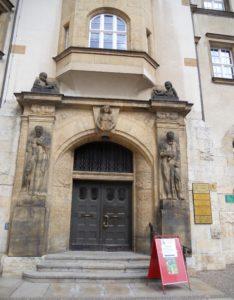 Über dem Eingangsportal hängt den Schlussstein markierend die Stadtpatronin Doblina, die das Stadtwappen trägt. Die Männerfiguren rechts und links des Eingangs sollen Klugheit und Tatkraft darstellen.