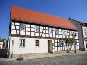 Dieses schicke Fachwerkhaus wurde 1754 als Umgebindehaus erbaut. 1965 waren Umgebinde aber nicht mehr so angesagt und deshalb entfernte man es. Von 2013 bis 2015 wurde das Haus aufwendig denkmalgerecht saniert. (Markt 15)