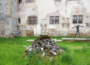 """Im Vordergrund ist die Skulptur """"Zugeschüttet"""" aus dem Jahr 1996 zu sehen."""