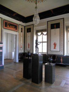 """Das Pompejanische Zimmer ist in seiner Ausmalung der Villa des Cicero in Pompeji nachempfunden. Als Vorlage dienten - wie bei vielen anderen antikisierenden Raumausmalungen des Schlosses - die Stiche des Buches """"Le Antichitá di Ercolano""""(1757-1792)."""