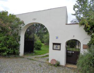 Die Toreinfahrt des Pfarrhauses. Rechts neben der Tür ist die Gedenktafel zu sehen.