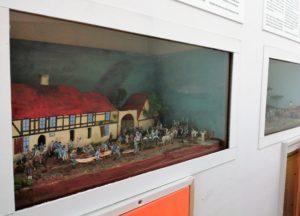 """Raum 3 - Die Zivilbevölkerung. In diesem Raum sind u. a. verschiedene Dioramen zu bewundern. Hier zu sehen ist das Diorama """"Österreichisches Feld-Lazarett um den 18. Oktober 1813 im Landgasthof und der Postausspanne Seifertshain"""" zu sehen."""