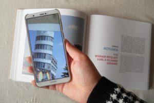 Eine Hand, die das Smartphone über das Buch hält. Mit dem Smartphone wird gerade die App zum Buch benutzt.