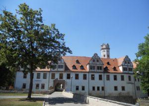 Schlossgebäude mit Bäumen und Steinbrücke